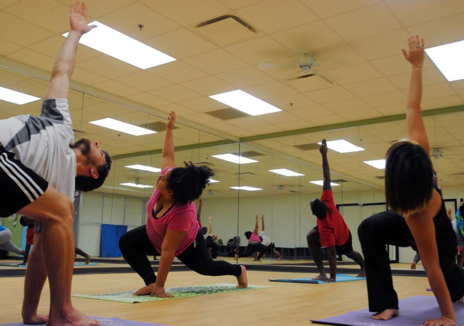 Robert Bemman, sophomore excercise science major, leads students Olivia Patton, senior humanities and geography double major, (front left) Amanda Head, sophomore dental hygiene major (front right) and Kenneth Pasley, sophomore communications major through  yoga poses March 27.