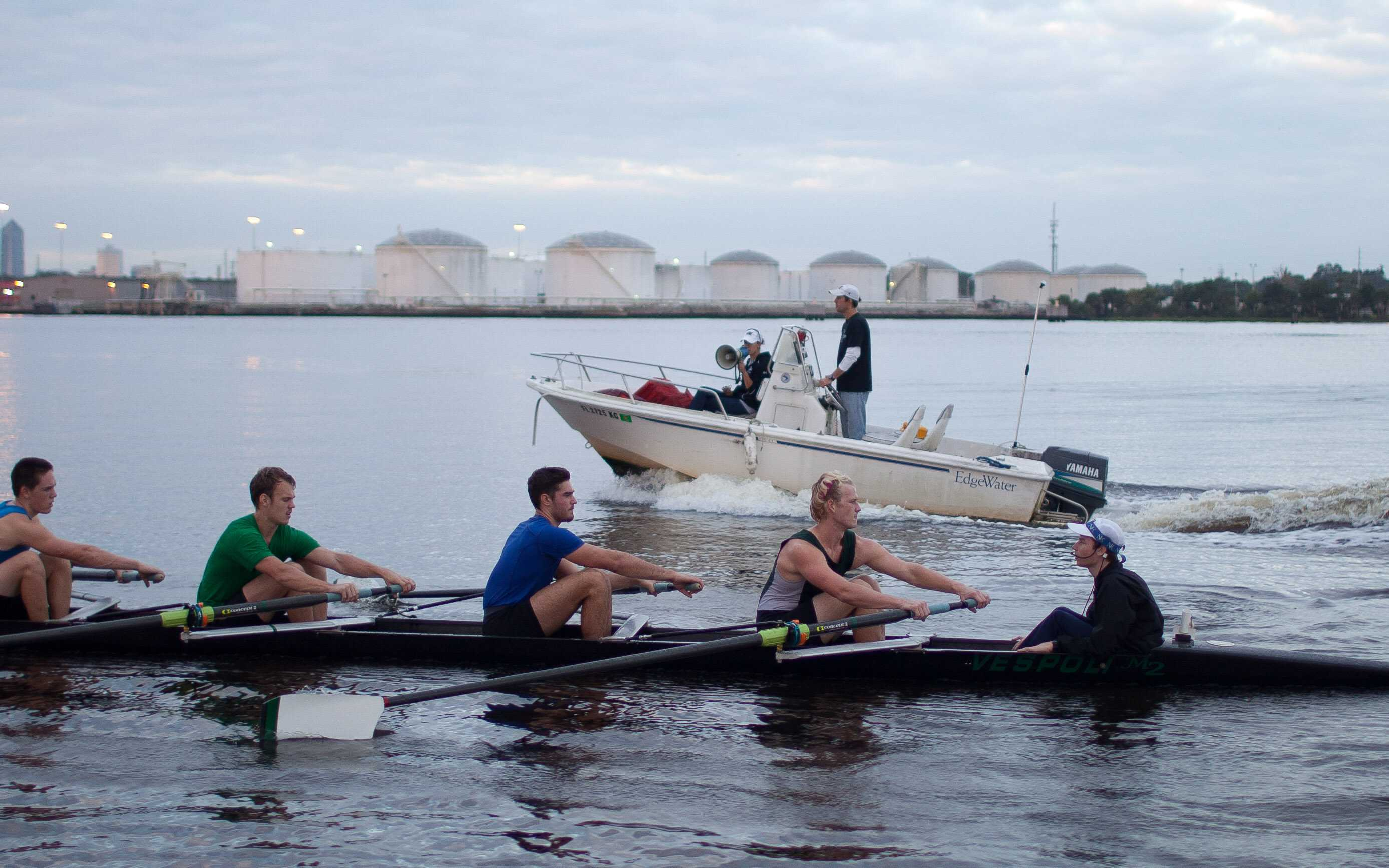 At an early morning practice Oct. 4, Coach Marci Robles gives direction from a megaphone as the team rows past her and Assistant Coach Rich Kelley in the coaching launch.