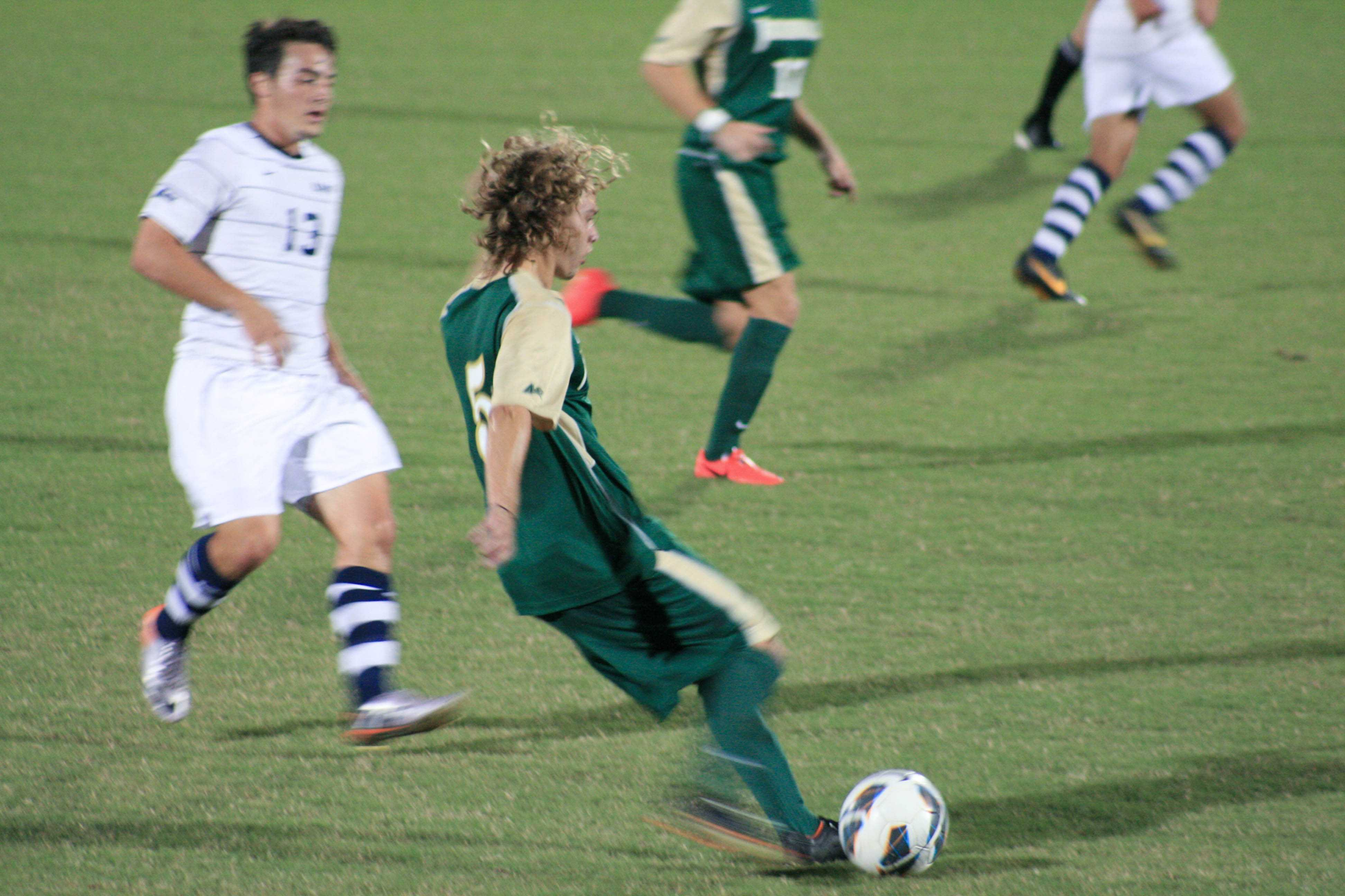 Junior captain Griffin Kelly crosses a pass down the pitch.