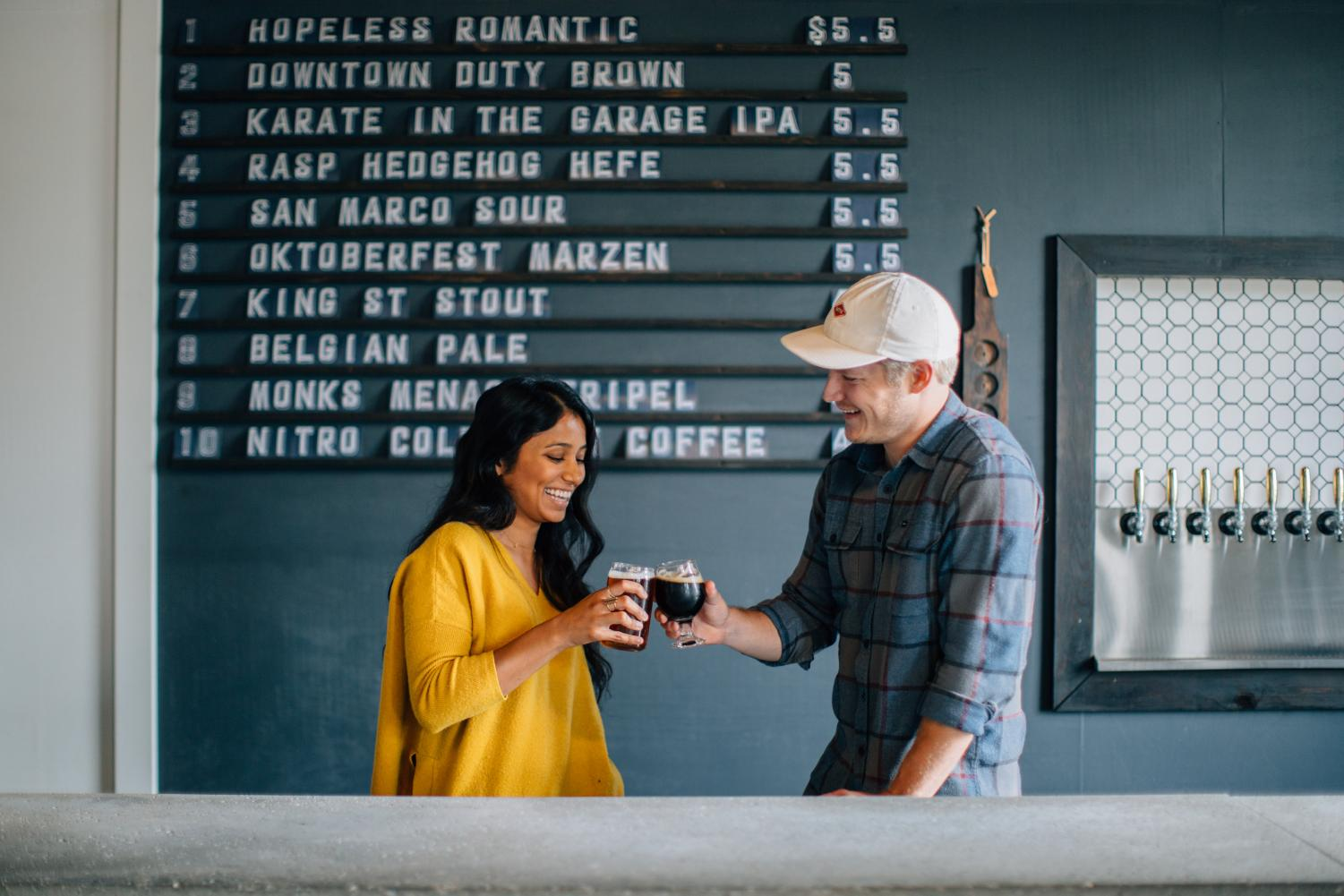 Alex and Priya Moldovan, owners of Town Beer Co., cheering as they have a glass of locally crafted beer.