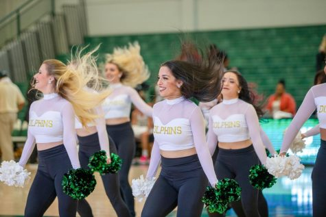 From left to right: Ally Lupinetti and Nikki Karadjov, members of the Sirens, performing pom dance during basketball game.