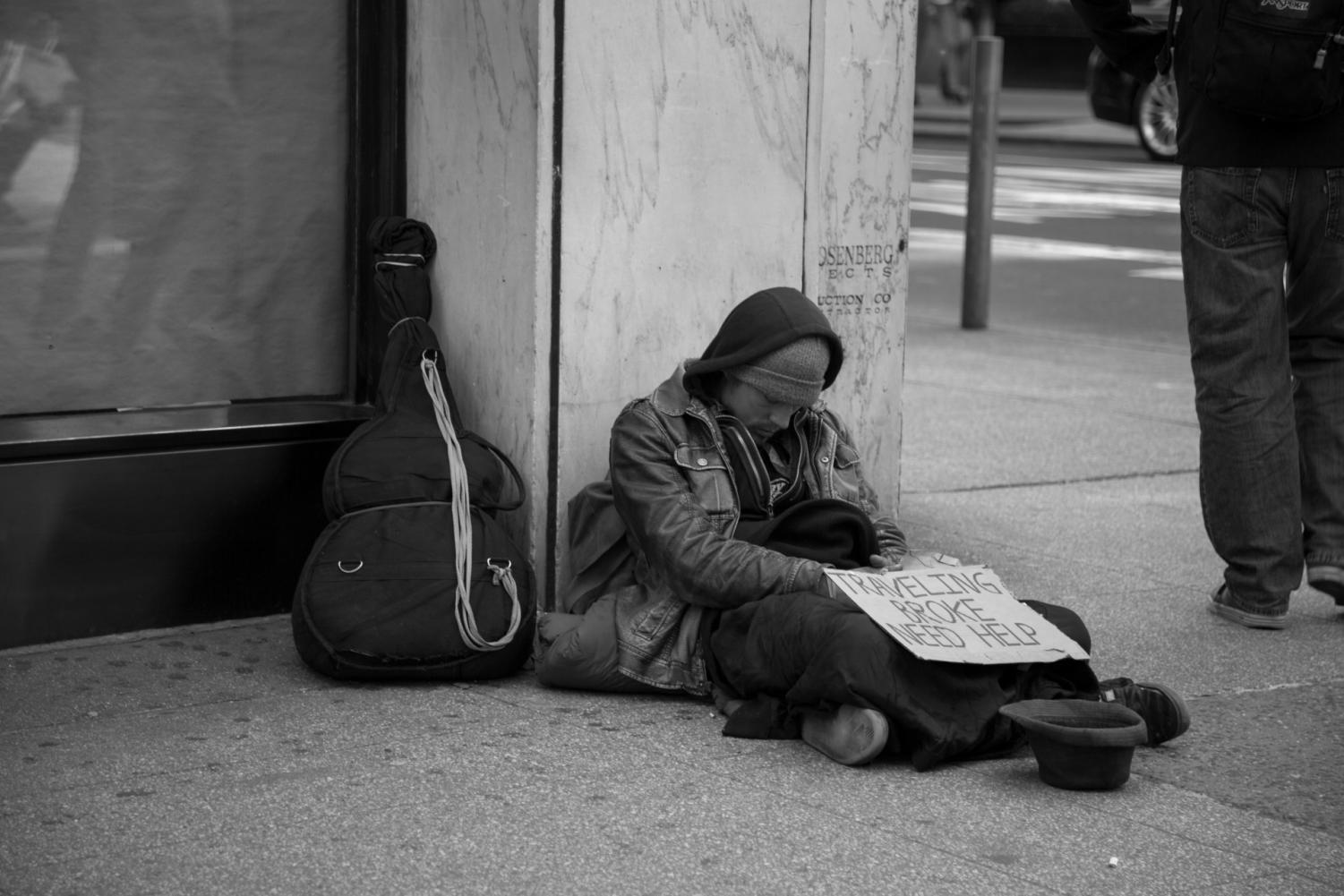 Homeless man sitting on street with sign.
