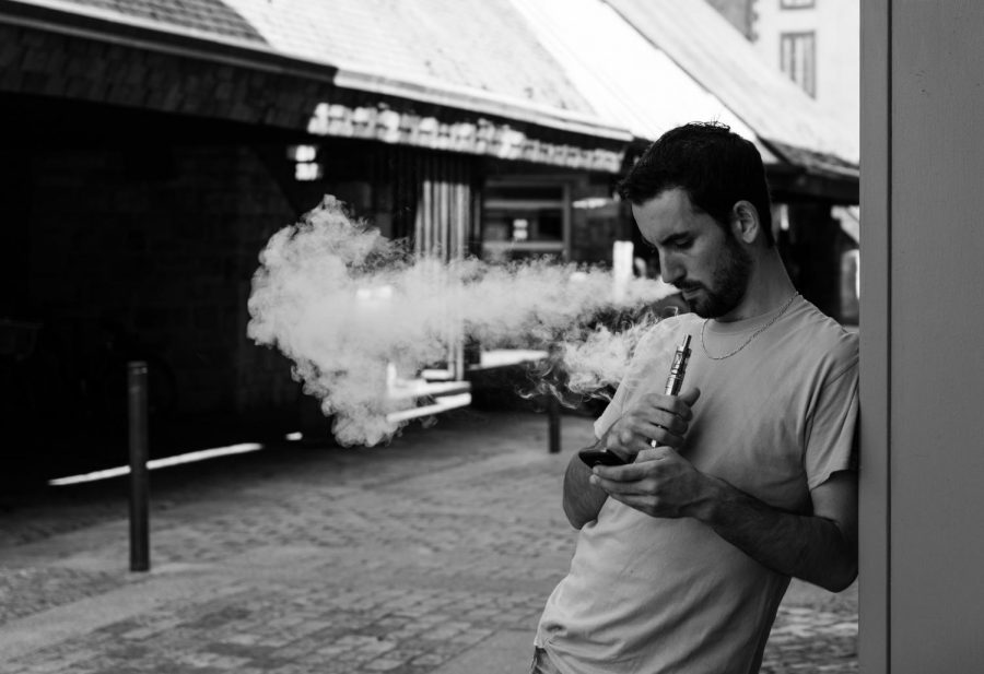Man uses e-cigarette while looking at his phone.